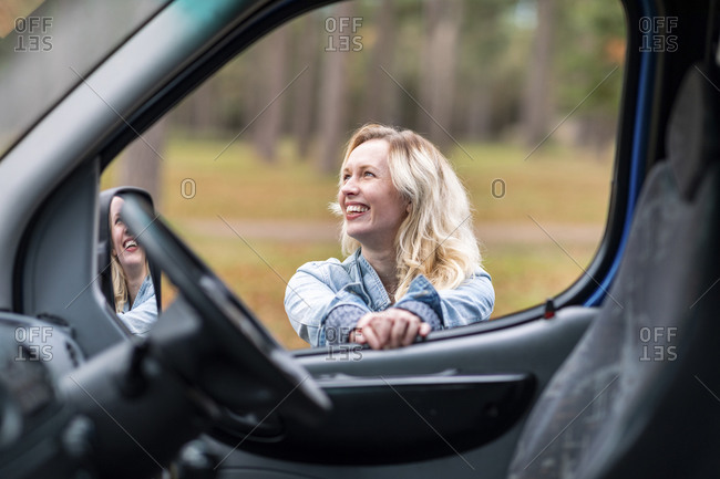 Cheerful woman seen from camper van window