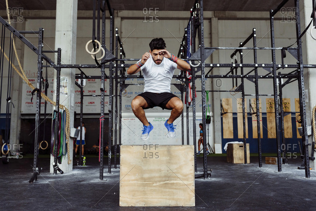 Young athlete exercising box jumps at gym
