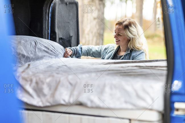 Smiling woman adjusting bed in motor home