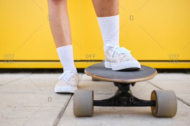 Feet of young woman standing on longboard