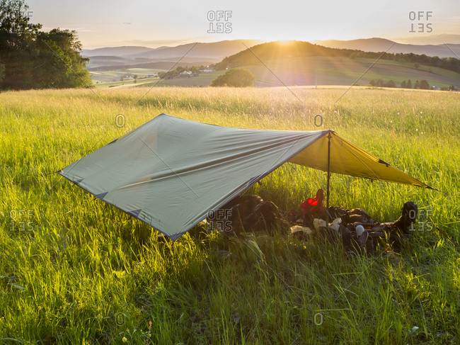 Tarpaulin set in alpine meadow at sunset