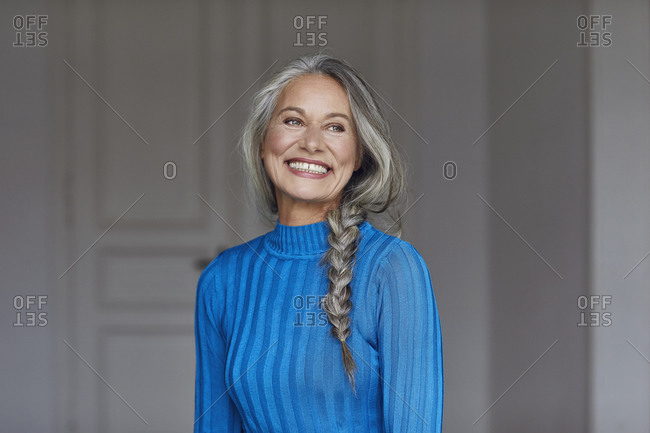 Happy mature woman looking away at home