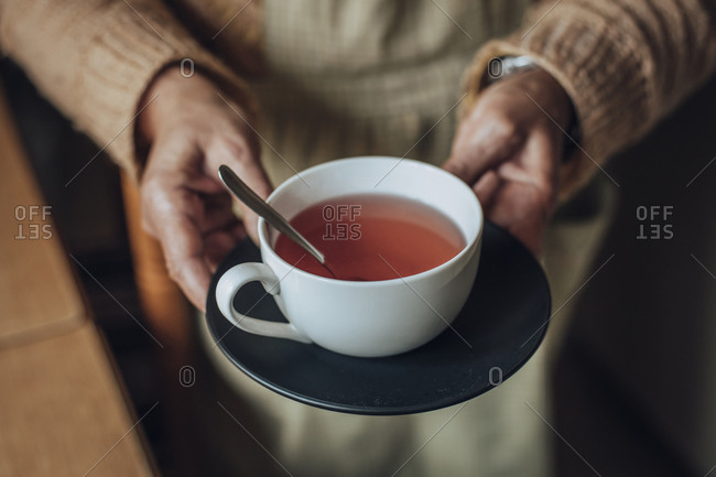 Senior woman's hands holding cup of tea