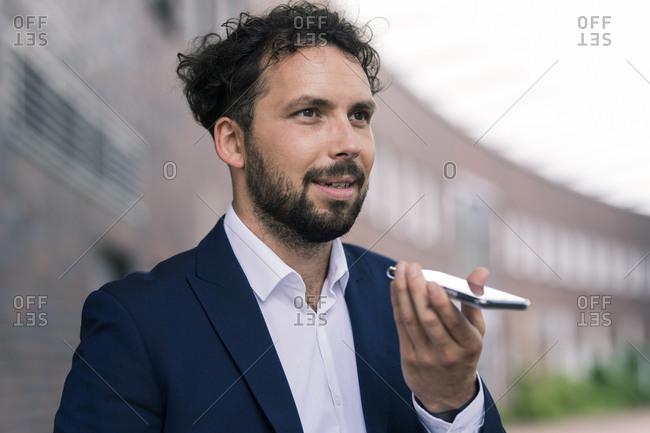 Businessman sending voicemail through mobile phone against building