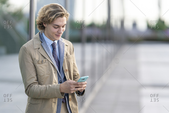 Young businessman using mobile phone while standing outdoors