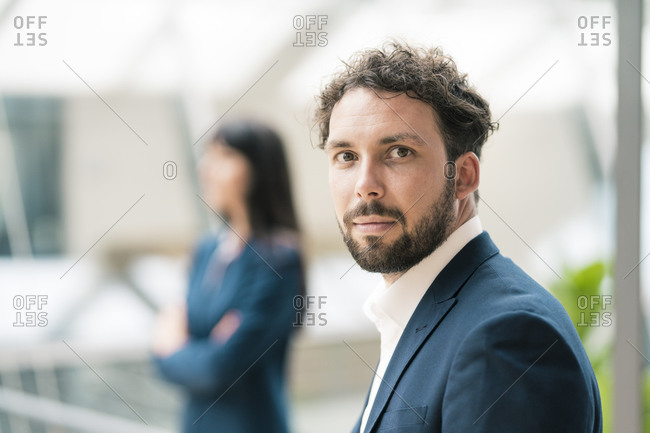 Confident businessman standing by female colleague in office