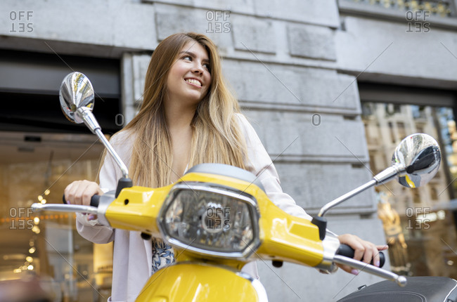 Smiling woman standing by moped motorcycle against building