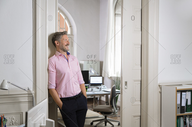 Businessman laughing with hands in pockets against doorway