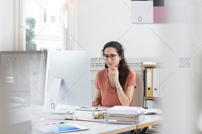 Female professional smiling while using computer in office