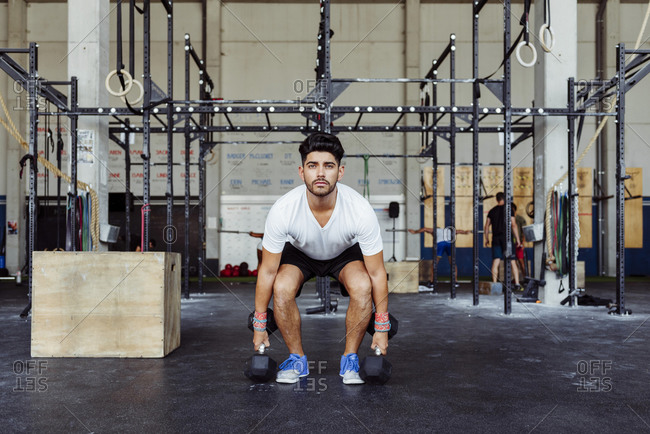 Sportsman exercising weight lifting with dumbbells at gym