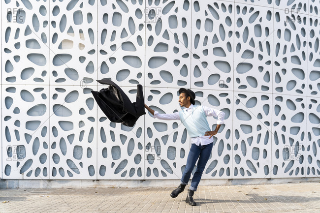 Fashionable man dancing with blazer against pattern wall