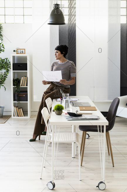 Businesswoman browsing documents at edge of office table