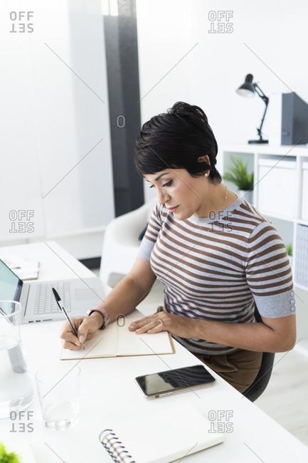 Portrait of businesswoman doing paperwork at office desk