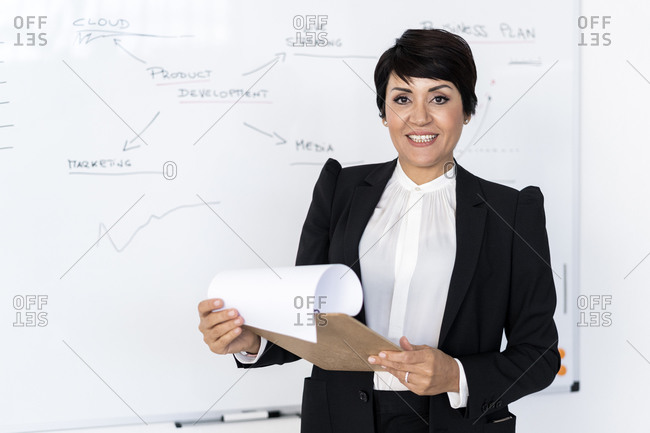 Portrait of businesswoman posing with documents in hands