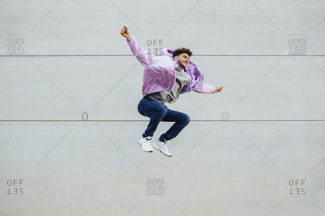Carefree man with arms outstretched jumping against wall