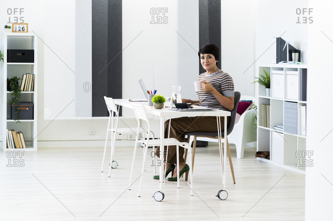 Portrait of businesswoman working alone at office table