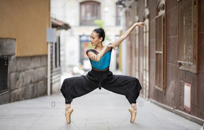 Female dancer dancing while standing tiptoe on footpath