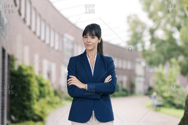 Businesswoman with arms crossed standing in office park