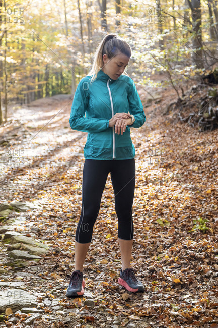 Sportswoman checking time while standing on forest path