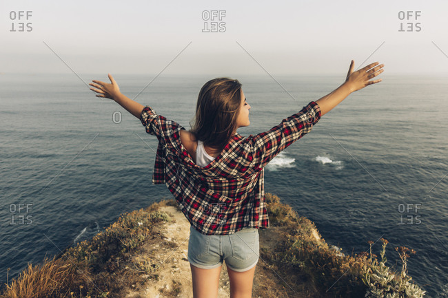Young woman standing with arms outstretched against sea