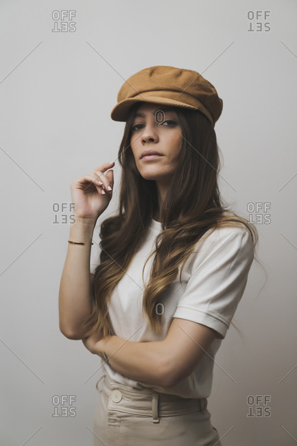 Young beautiful woman wearing cap standing against wall