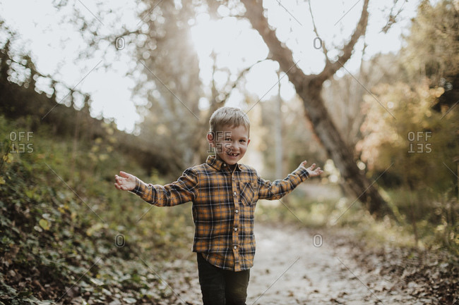 Carefree boy standing with arms outstretched in forest