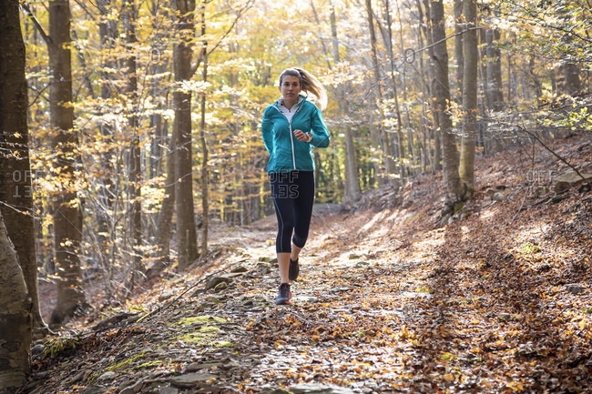 Athlete exercising while running on footpath in forest