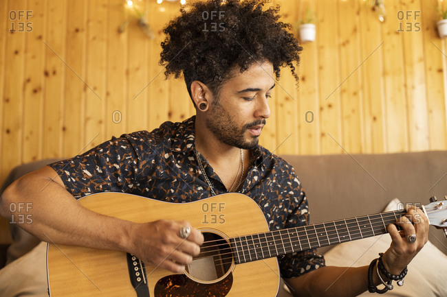 Male guitarist playing guitar while rehearsing at home