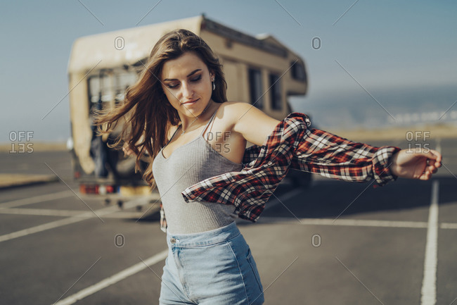 Carefree woman standing with arms outstretched on road