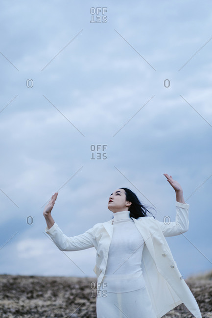Thoughtful woman standing with hand raised against sky