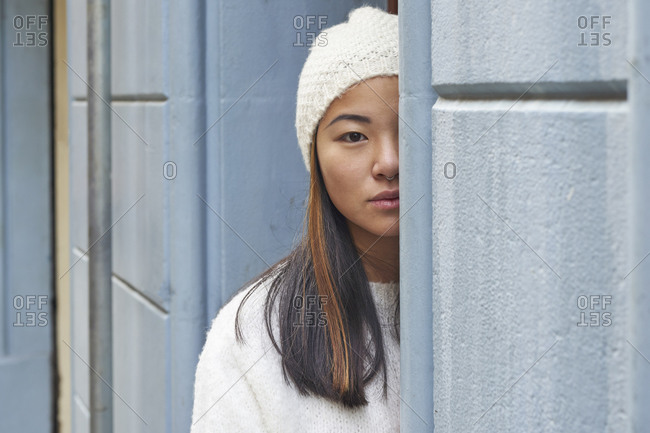 Young woman hiding behind wall while standing outdoors