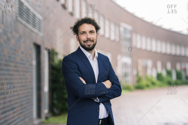 Businessman with arms crossed standing at office park