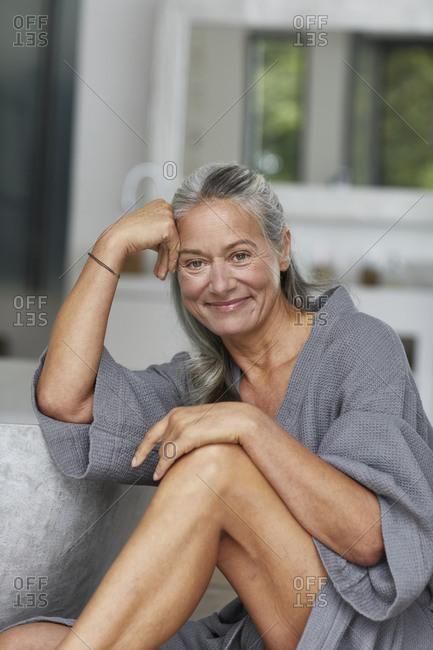 Beautiful mature woman leaning by bathtub in bathroom