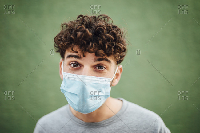 Young man with surgical mask against green background