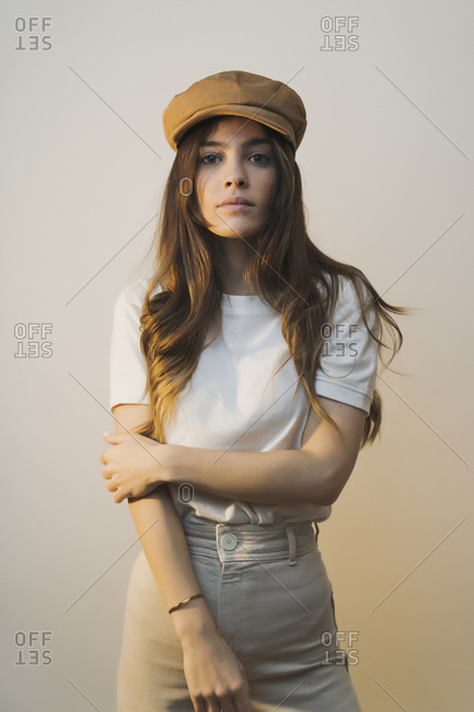 Woman wearing cap staring while standing against wall