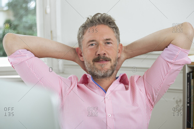 Smiling businessman with hands behind head in office
