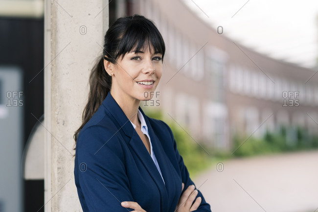 Smiling female entrepreneur by column at office park