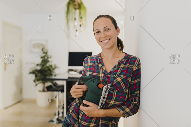 Woman smiling while holding electric jigsaw at home