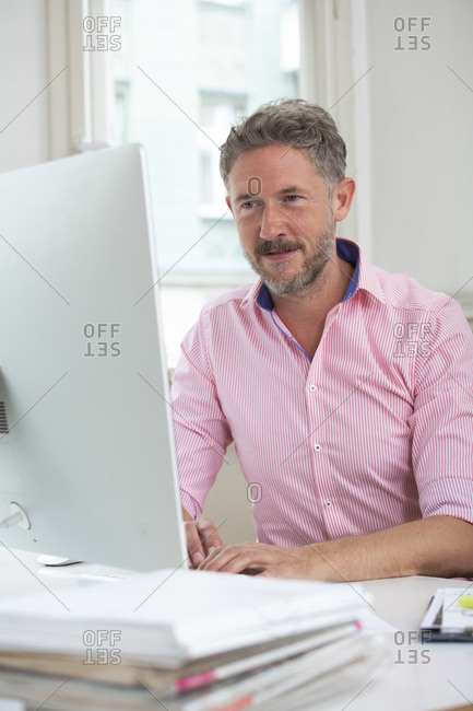 Male professional working on laptop in office cabin