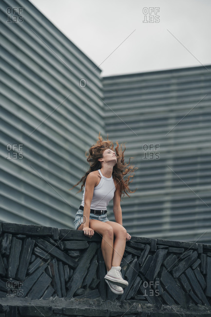 Young woman tossing hair while sitting against wall