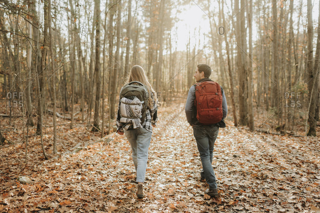 Young couple hiking with backpacks in autumn forest