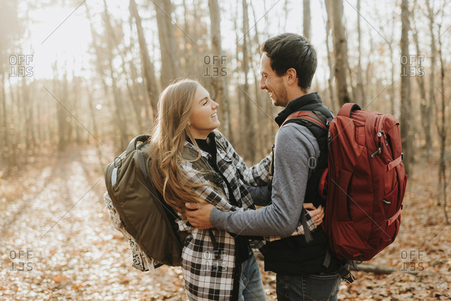 Young couple embracing in forest during autumn hike