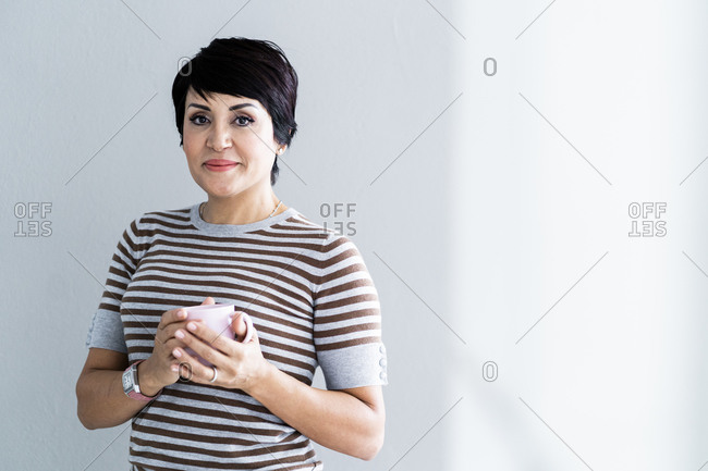 Portrait of businesswoman posing with mug in hands