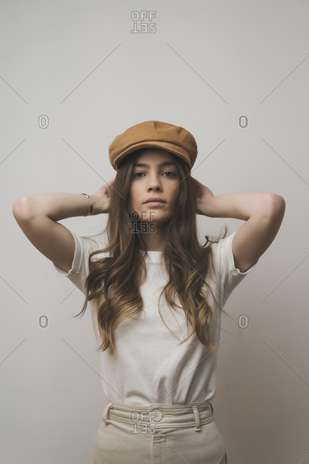 Woman with hands behind head standing against wall