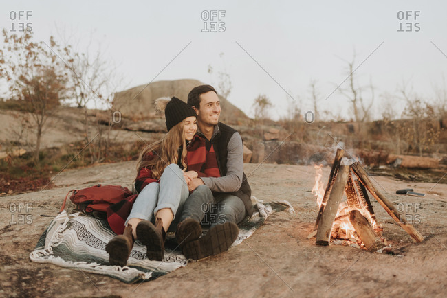 Young couple sitting together in front of campfire
