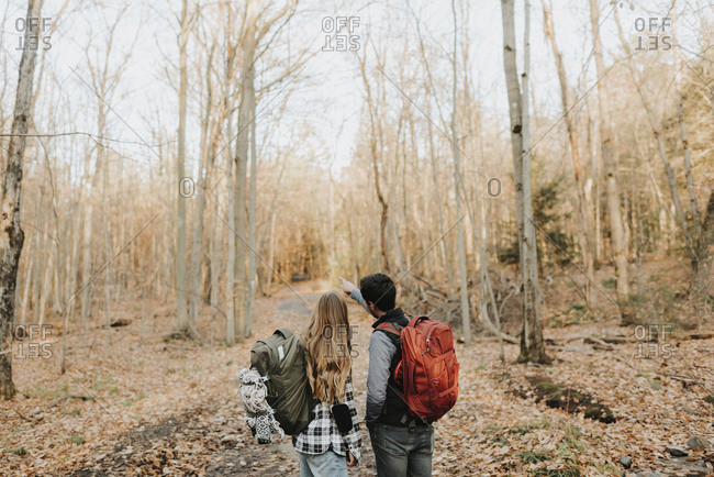 Young couple standing in forest during autumn hike