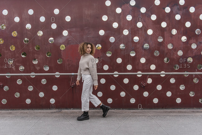 Young blond woman walking by maroon metallic wall