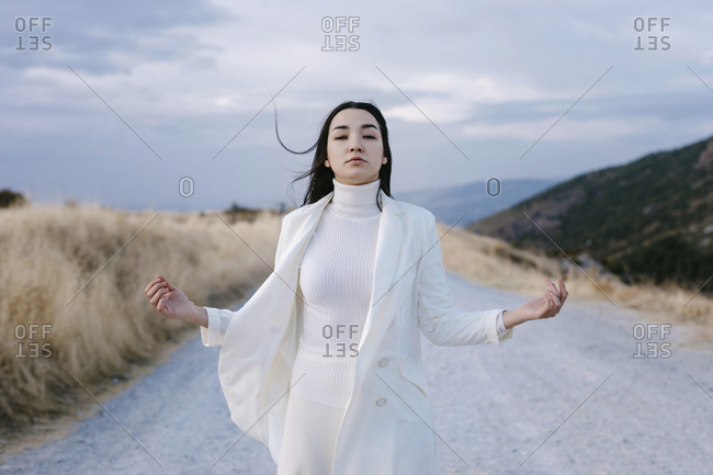 Young woman wearing white jacket standing on road