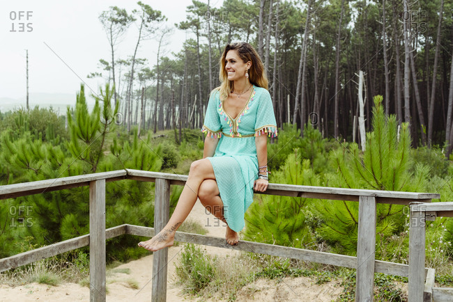 Woman smiling while sitting on railing at forest