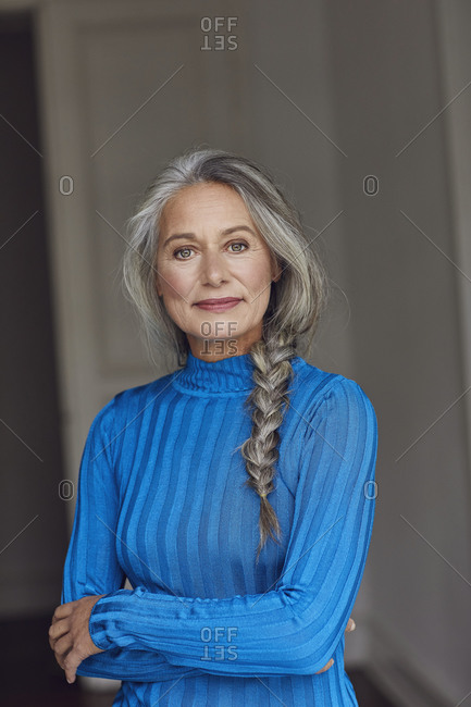 Confident mature woman with arms crossed at home
